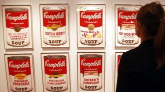 Sotheby's staff member Isabelle Brown looks at a set of Andy Warhol's Campbell's Soup screenprints at the Sotheby's auction rooms in London